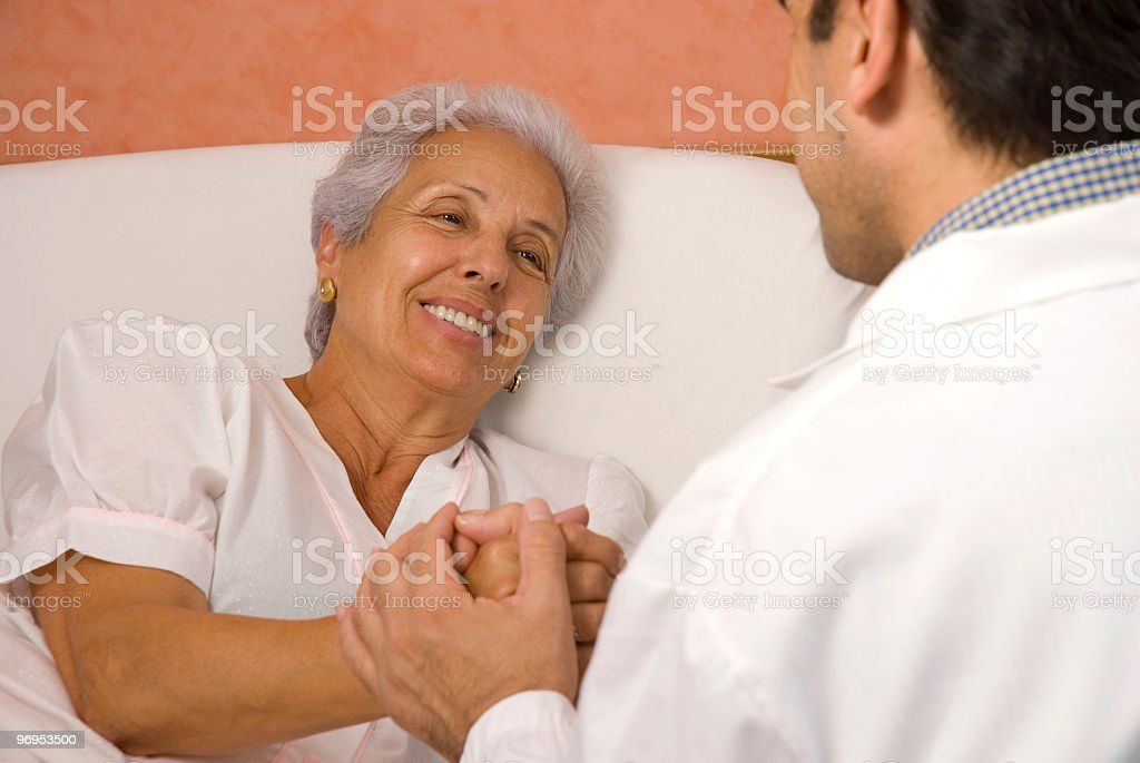 Senior patient holds hands with male doctor royalty-free stock photo