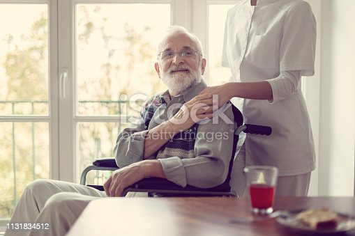 istock Senior patient in nursing home with helpful nurse in white uniform 1131834512
