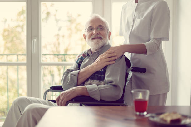 senior patient in nursing home with helpful nurse in white uniform - cancer patient stock pictures, royalty-free photos & images