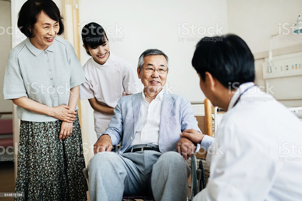 Senior Patient in Wheelchair with Family and Doctor stock photo