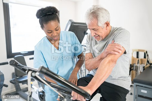 istock Senior patient listeninig to his black physiotherapist teaching him the correct posture on the static bicycle 912333752