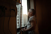 istock Senior patient looking through window at hospital 1236341676