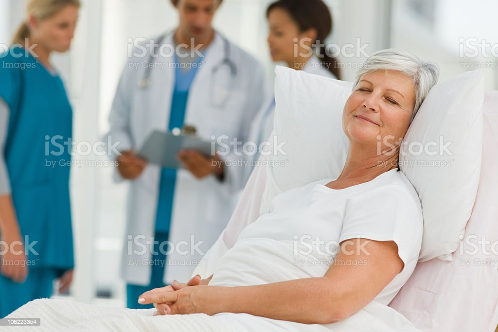 Senior patient lying on bed with doctors in background - Royalty-free 20-24 Years Stock Photo