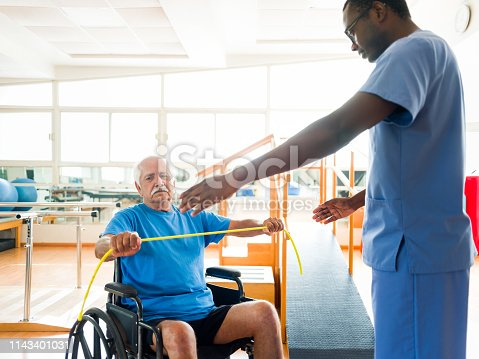 istock Senior patient on wheelchair stretching arms with elastic band 1143401031