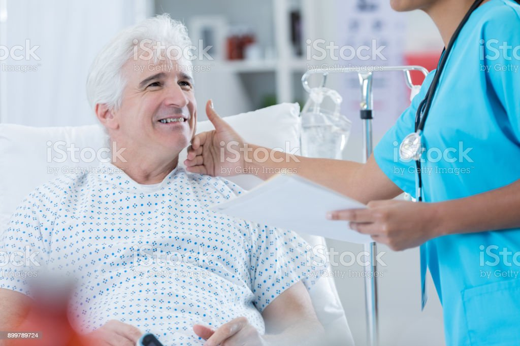 Senior adult Caucasian man smiles up at African American nurse or...