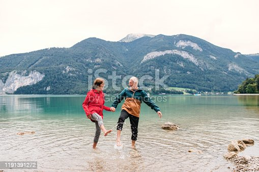 A senior pensioner couple hikers standing barefoot in mountain lake in nature.