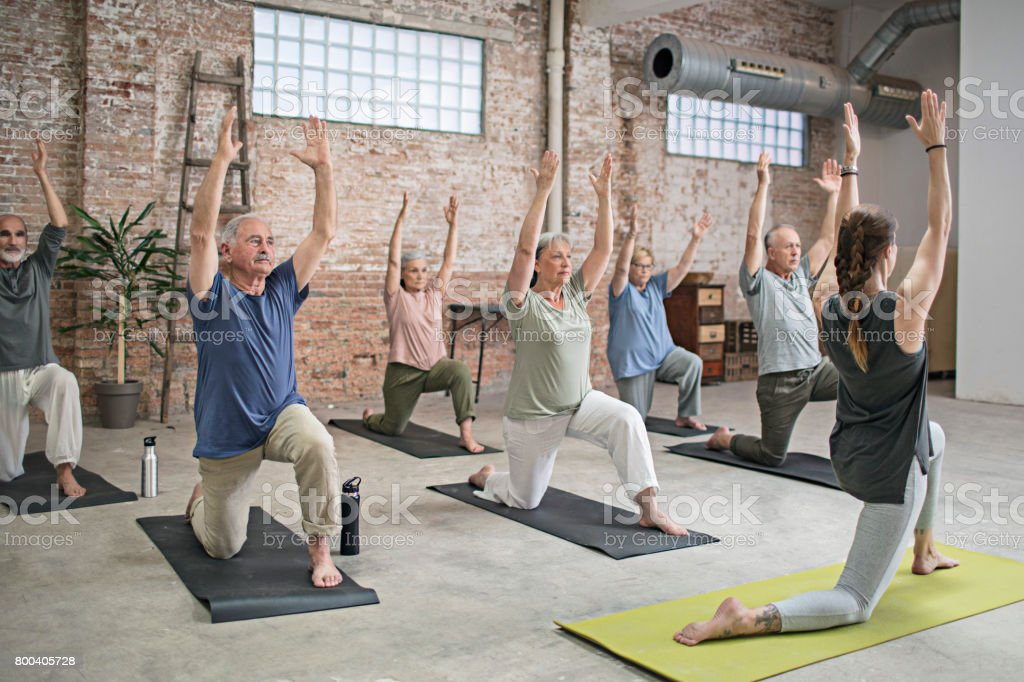 Senior people and coach doing warrior pose in gym stock photo