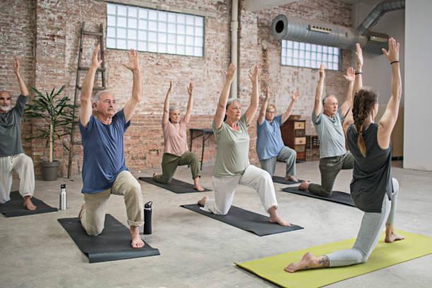 Senioren und Trainer tun Krieger stellen in Fitness-Studio – Foto