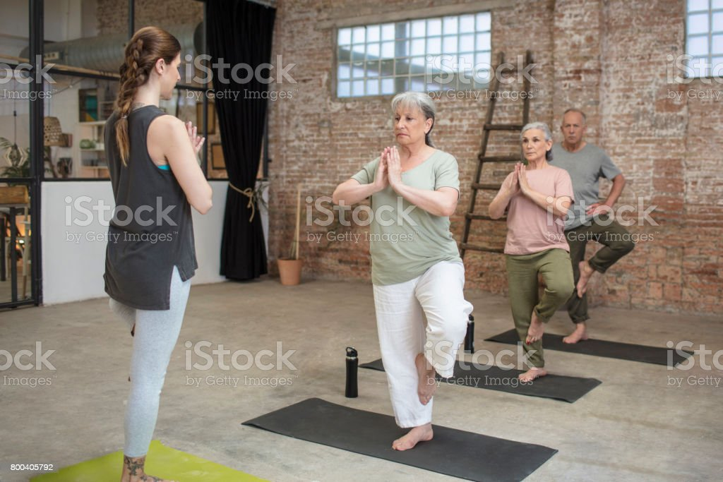 Senior people and coach exercising in tree pose stock photo