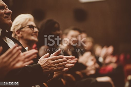 585298714 istock photo Senior people clapping in the theater, focus on hands 1214333105