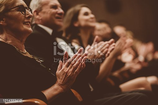 585298714 istock photo Senior people clapping in the theater, focus on hands 1214333412