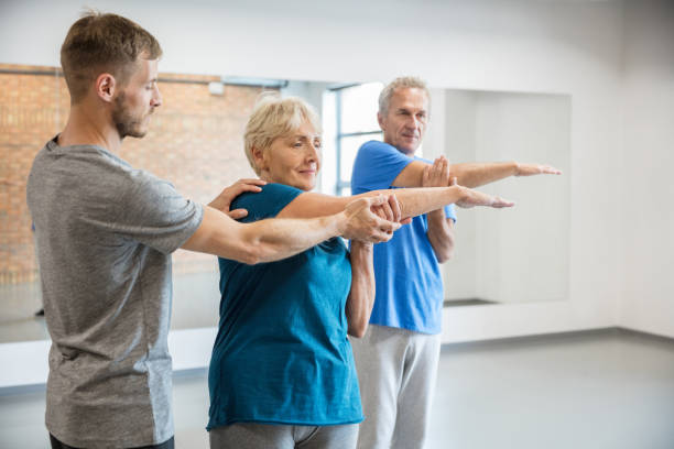 Senior people exercising with trainer at rehab club Senior people exercising at gym with trainer helping woman while doing arms workout. Old man and woman under going fitness training at rehab club. drug rehab stock pictures, royalty-free photos & images