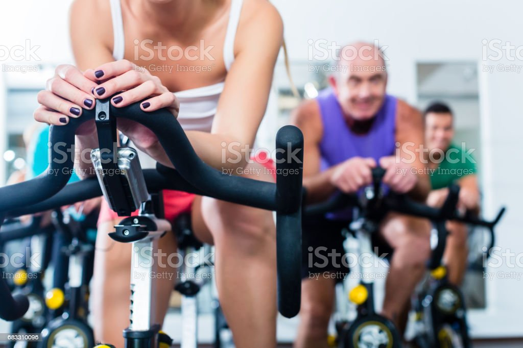 Senior people in gym spinning on fitness bike foto stock royalty-free