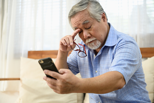 Senior people lifestyle health problem concept : Portrait photo of senior Asian man has a eye long sighted problem trying to read message from smartphone.