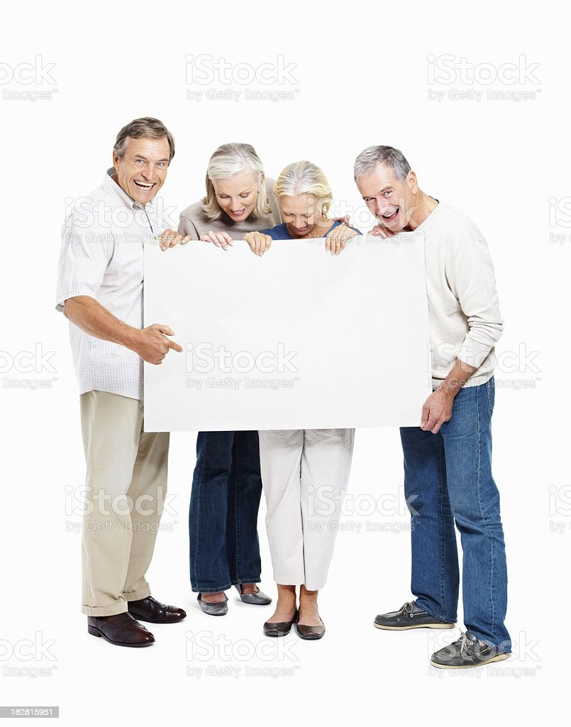 Senior people looking at a blank placard against white royalty-free stock photo