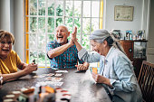 Group of people, senior people playing cards in nursing home.