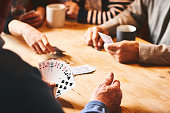 Close up of senor man's hand playing cards with friends at care home