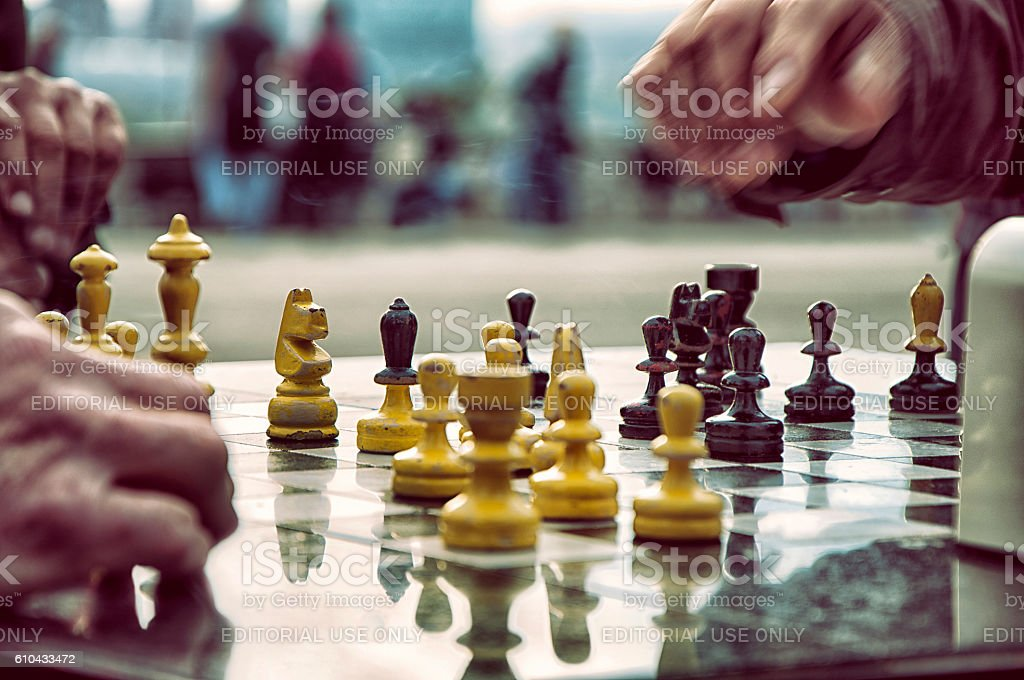 Senior people playing chess on a bench outdoors. stock photo