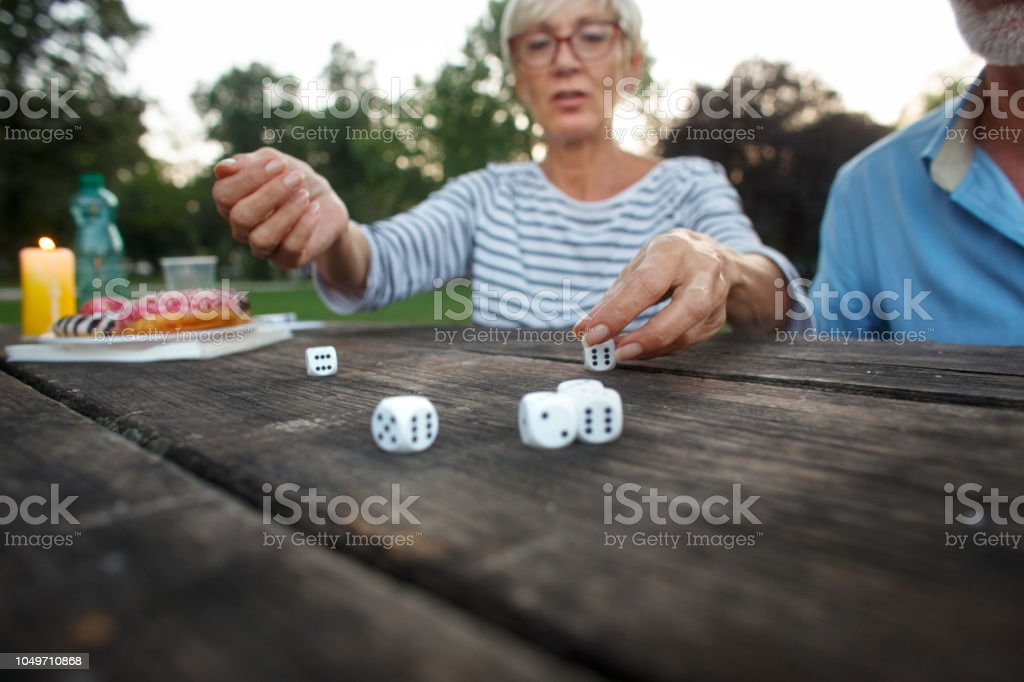 Group of active senior people playing dice game during a picnic day.