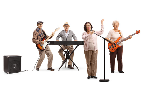Senior people playing in a band an an elderly lady singing on a microphone