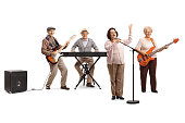 Full length portrait of senior people playing in a band an an elderly lady singing on a microphone isolated on white background