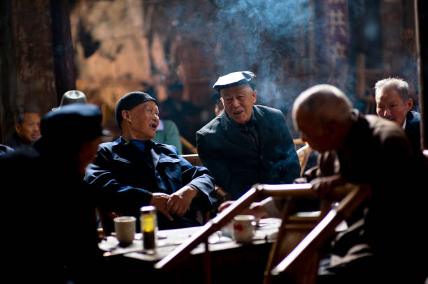 "Senior people relaxing in traditional tea house, Chengdu, China ""Chengdu, China - April 30, 2012: Senior people are relaxing in an old tea house in the county of Chengdu, which is considered as one of the most relaxing cities in China. There are countless tea houses in the city."" tea room stock pictures, royalty-free photos & images"
