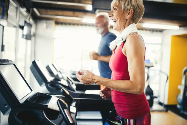 Senior people running in machine treadmill at fitness gym club stock photo