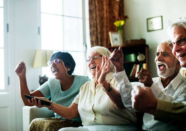 Senior people watching television together Senior people watching television together retirement community stock pictures, royalty-free photos & images