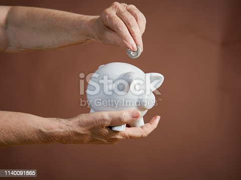 A senior person's hand adds a single coin to a piggybank.