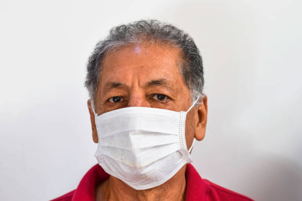 senior peruvian man suffers from cough with face mask protection, elderly man with facial mask due to air pollution, sick elderly with medical mask, pollution - covid hair imagens e fotografias de stock