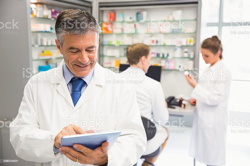 Senior pharmacist using tablet pc stock photo
