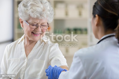 istock Senior pharmacy customer gets a band-aid after flu shot 807443180