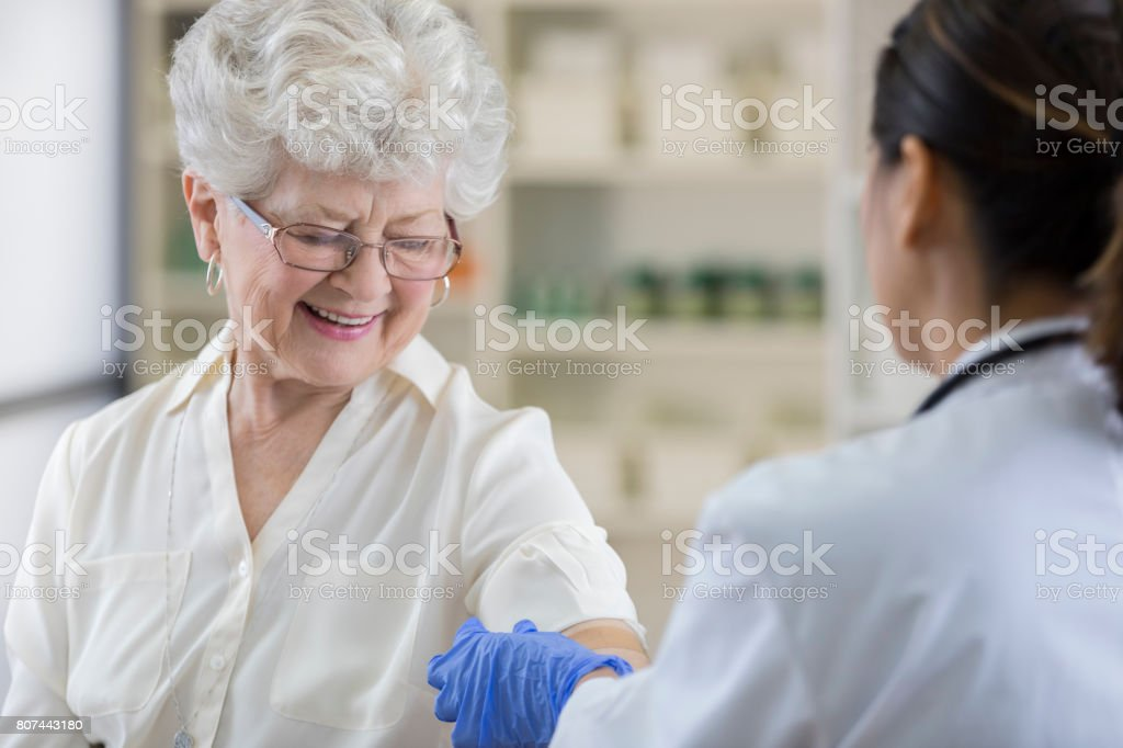 Senior pharmacy customer gets a band-aid after flu shot stock photo