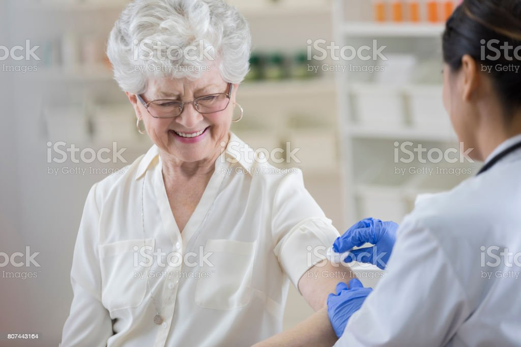 Senior pharmacy customer smiles nervously before flu shot stock photo