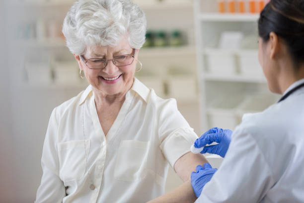Senior pharmacy customer smiles nervously before flu shot An attractive senior woman is at the pharmacy getting a flu shot.  She smiles nervously and looks down at her upper arm as the gloved pharmacist cleans it with cotton and alcohol.  There are shelves in the background. flu shot stock pictures, royalty-free photos & images