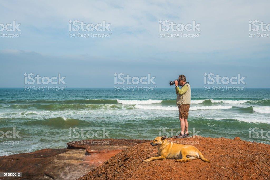 Senior Photographer and Orange Dog on the Atlantic Coast, Legzira, Sidi Ifni, Morocco, North Africa stock photo
