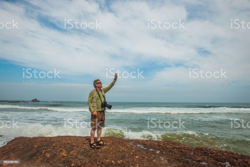 Senior Photographer on the Atlantic Coast Taking Selfie,  Legzira, Sidi Ifni, Morocco, North Africa stock photo