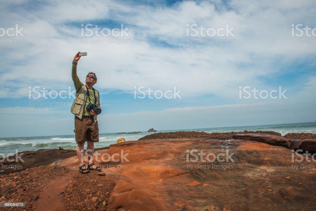 Senior Photographer on the Atlantic Coast Taking Selfie of Himself and the Dog,  Legzira, Sidi Ifni, Morocco, North Africa stock photo