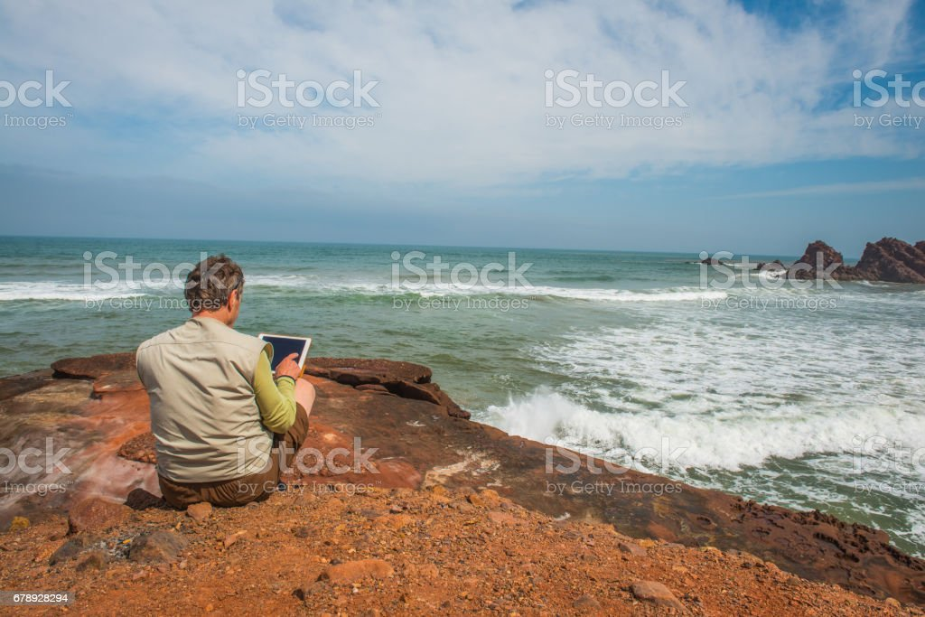 Senior Photographer Surfing on Digital Tablet, the Atlantic Coast, Legzira, Sidi Ifni, Morocco, North Africa stock photo