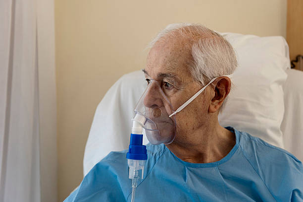 Senior Elderly man with an oxygen mask, looking through a window. oxygen mask stock pictures, royalty-free photos & images