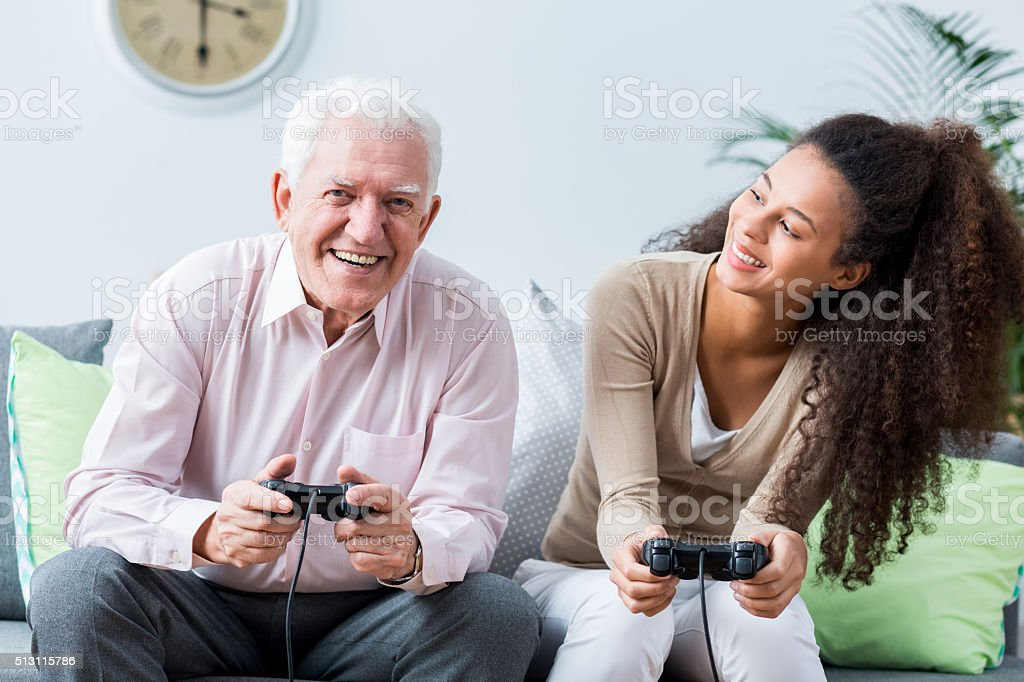 Senior playing on the console stock photo