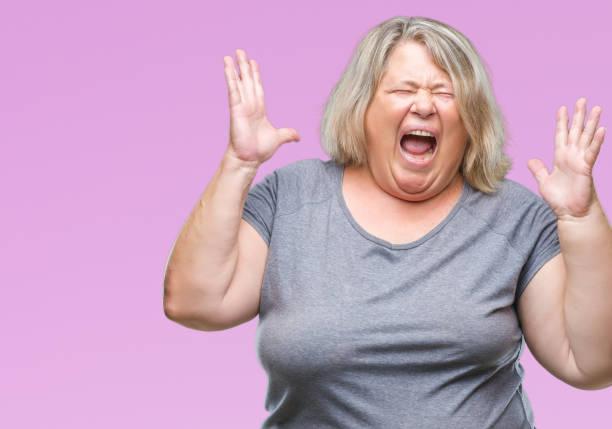 senior plus size kaukasischen frau über isolierte hintergrund crazy und verrückt schreien und schreien mit aggressiven ausdruck und erhobenen armen. frust-konzept. - ausgefallene mode für mollige stock-fotos und bilder
