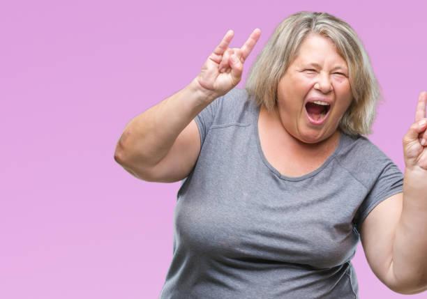 senior plus größe kaukasischen frau über isolierte hintergrund mit verrückten ausdruck tun rock symbol mit händen oben schreien. musik-star. schwere konzept. - ausgefallene mode für mollige stock-fotos und bilder