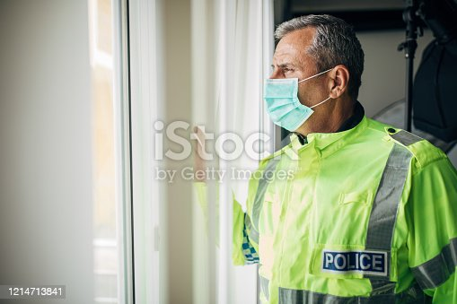 Senior British police officer with protective mask looking through the window from the office. Fight against coronavirus.
