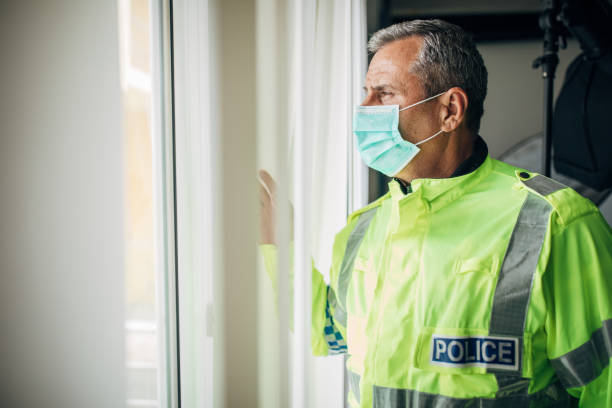 Senior police officer with protective mask stock photo