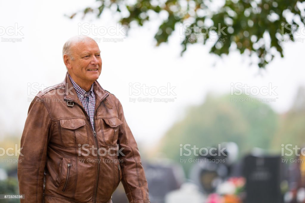 Senior Portrait - 73 years old man in leather jacket walking outdoors in autumn stock photo