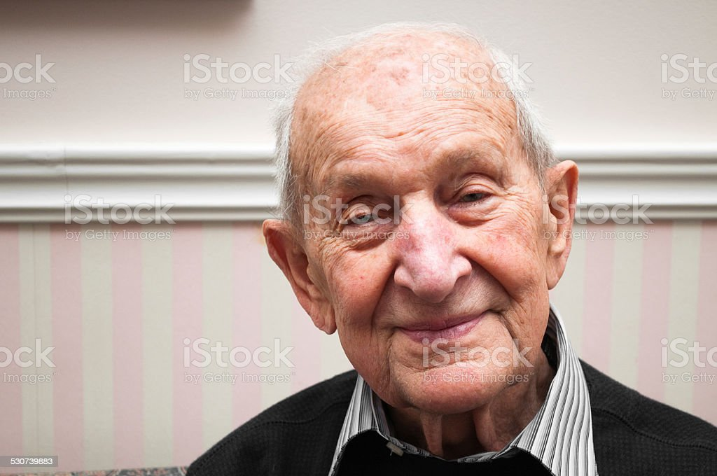 Senior portrait of a man smiling in his living room stock photo