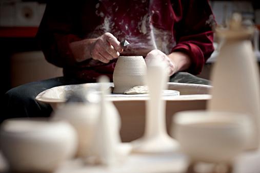 Senior potter hands working on clay jar