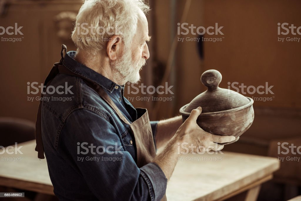 Senior potter in apron examining ceramic bowl at workshop foto de stock royalty-free