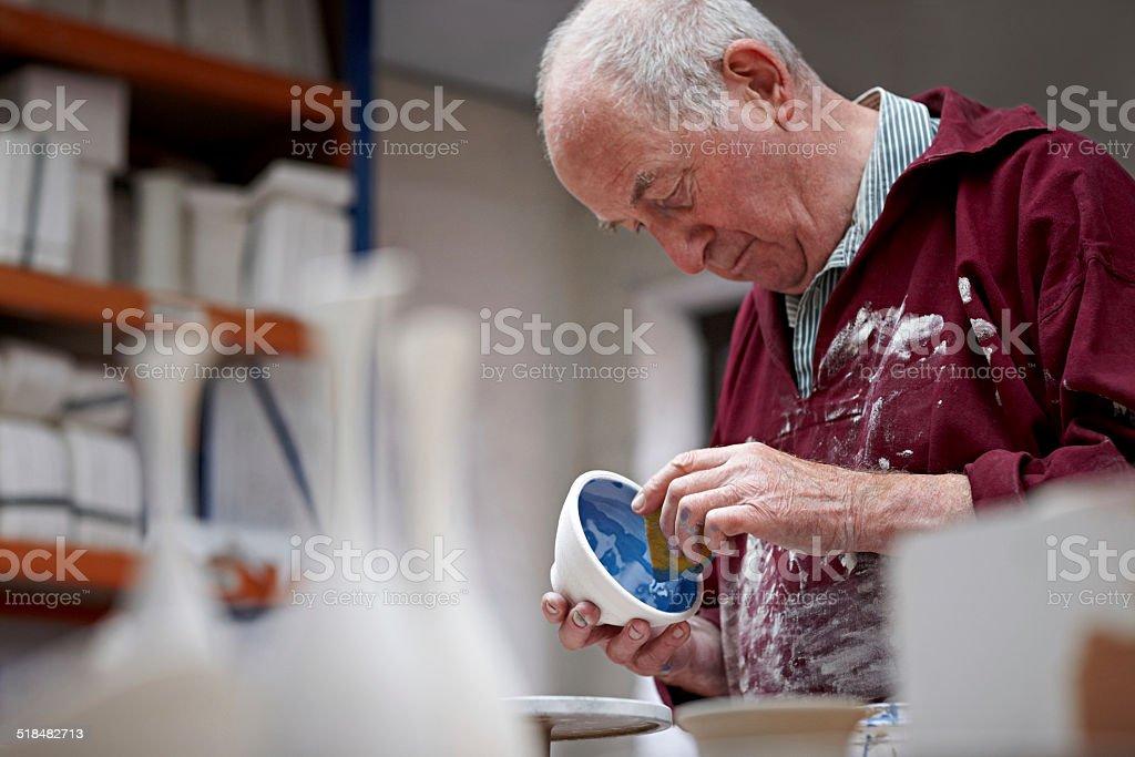 Senior potter painting a clay pot at workshop stock photo